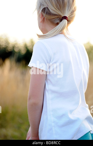 Royalty free photograph of a girl enjoying a summer evening camping in British national park and looking at sunset - Stock Photo