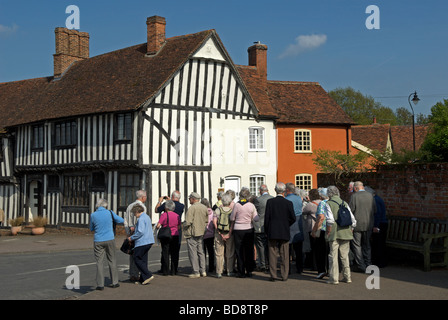 Group of tourists on a tour of Lavenham, Suffolk, UK. - Stock Photo