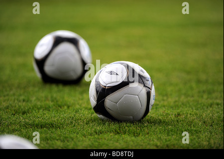 Two footballs on a football pitch