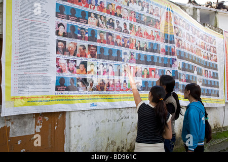 Tibetan women looking a poster showing Tibetans executed or imprisoned in Tibet. McLeod Ganj. Dharamsala. India - Stock Photo