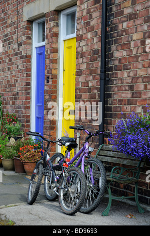 Durham City  yellow and blue door with two bikes outside the front door of a terraced house Wanless terrace - Stock Photo