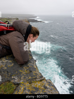 Looking down, Way down. On a stormy day a young woman dressed in a billowing jacket peers over the cliff to the - Stock Photo