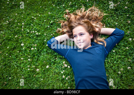 Girl 8-12 years old lies in a grassy field daydreaming - Stock Photo