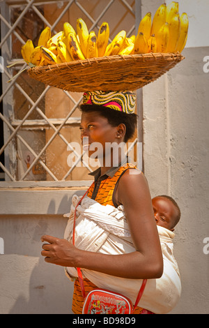 An Rwandan woman walks through downtown Kigali selling bananas with a child in a sling on her back - Stock Photo