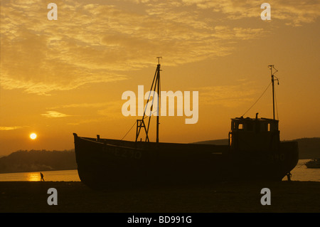 A beached fishing boat at sunset on the Exe estuary, Dawlish Warren, Devon, England - Stock Photo