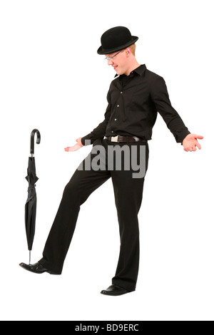 young man with bowler hat balancing an umbrella - Stock Photo