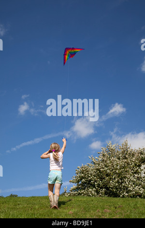Young girl flying red kite in blue sky Broadway Tower UK - Stock Photo