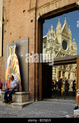 Tourist man sits in the shade outside the museum of Santa Maria della Scala with the Duomo (cathedral) reflected - Stock Photo