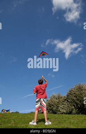 Boy flying red kite in blue sky Broadway Tower UK - Stock Photo
