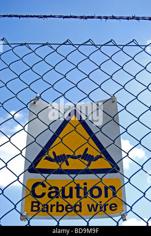 caution barbed wire sign on a fence at chiswick polytechnic stadium, chiswick, west london, england - Stock Photo