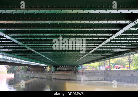 Lines of rivets in steel girders on underside of railway bridge over river - Stock Photo