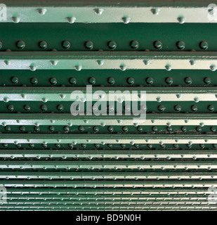 Lines of rivets in steel girders on underside of railway bridge over river close up - Stock Photo
