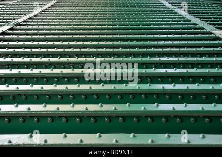 Lines of rivets in steel girders on underside of railway bridge over river close up inverted - Stock Photo