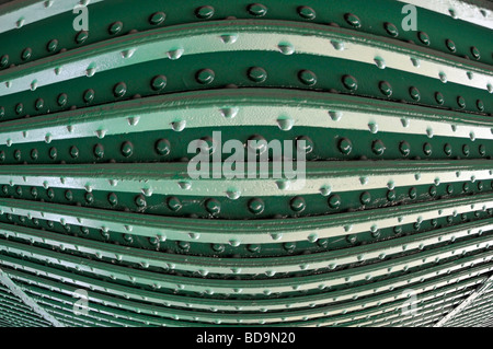 Rivets in steel girders on underside of railway bridge close up as pattern abstract background image manipulated