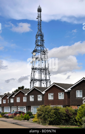 Telecommunications mast rising above row of houses - Stock Photo