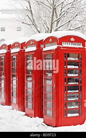 Snow on red telephone boxes London England - Stock Photo