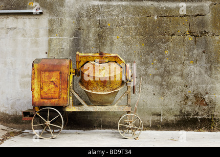 an old cement mixer in front of a concrete wall, landscape format - Stock Photo