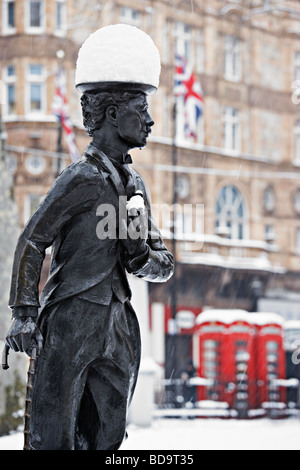 Snow on Charlie Chaplin statue Leicester Square London England - Stock Photo