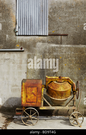 an old cement mixer in front of a concrete wall - Stock Photo