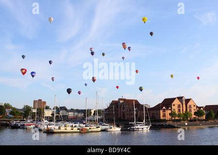 Bristol International Balloon Fiesta hot air balloons float over Bristol city harbour waterfront marina in August 2009