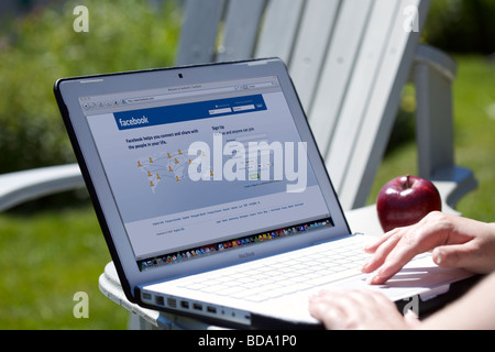 Female using laptop showing social networking Facebook splash screen page - Stock Photo