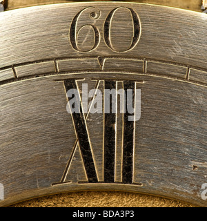 old antique clock face showing 60 and XII - Stock Photo