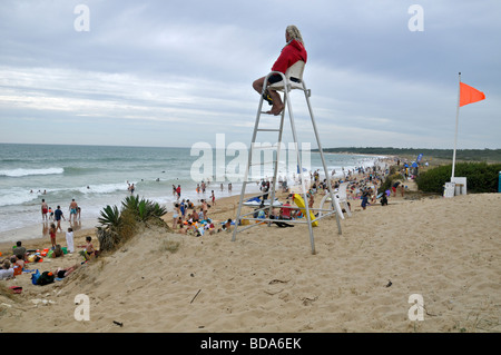 Supervised swimming. Sitting on his watch chair, the lifeguard watches swimmers on the beach. The orange flag signals - Stock Photo