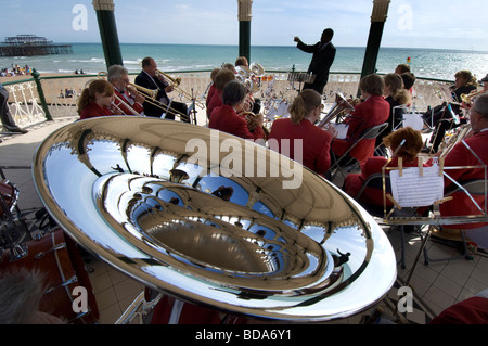 A  conductor leads the Patcham silver band in a concert on Brighton bandstand with a closeup of a tuba in the foreground. - Stock Photo