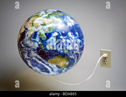 Still shot of a world globe plugged into an electrical outlet - Stock Photo