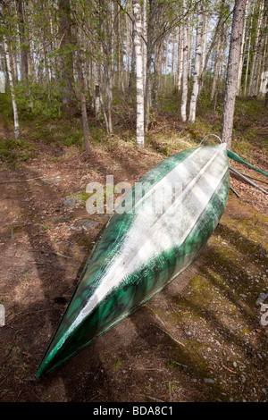 Upturned old green canoe in the forest , Finland - Stock Photo