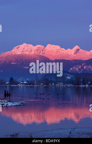 Sun setting on Golden Ears reflected in Pitt River, waterfowl fly low over the river, Port Coquitlam, British Columbia, - Stock Photo