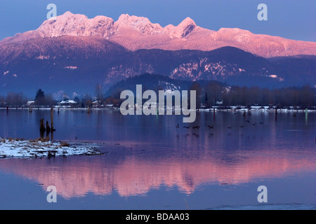 Sun setting on the Golden Ears reflected in the Pitt River with flock of geese, Port Coquitlam, British Columbia, - Stock Photo