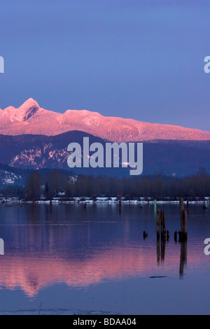Sun setting on the Golden Ears reflected in the Pitt River, Port Coquitlam, British Columbia, Canada - Stock Photo