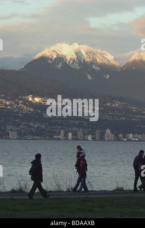 Walkers silhouetted against Burrard Inlet with North Vancouver and snow capped North Shore mountains behind - Stock Photo