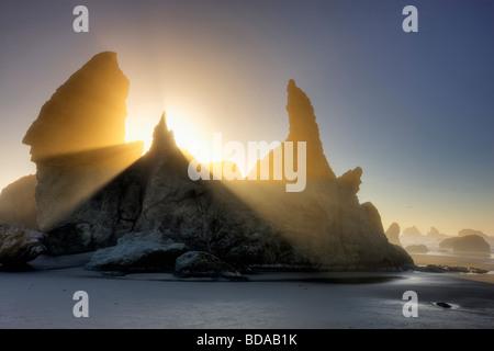 Sea stacks at Bandon Beach with fog and sun rays Oregon - Stock Photo