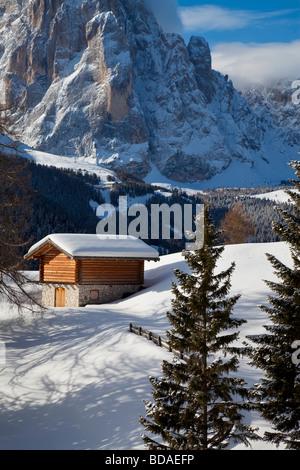 Winter snow covered mountain hut in front of Sassolungo mountain 3181m Val Gardena Dolomites South Tirol Trentino - Stock Photo