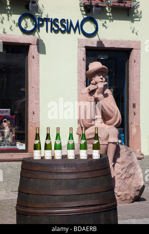 Ribeauville Alsace Haut Rhin France Display of wine bottles on an old wooden barrel beside a statue on Alsatian - Stock Photo
