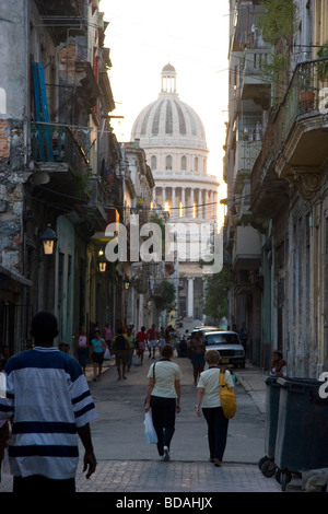 Havana residents walk down alleyway with Capitolio dome in the distance. - Stock Photo