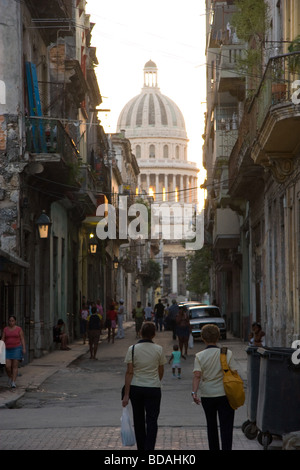Late afternoon light streams in through the top of the Capitolio dome as Havana residents walk home from work - Stock Photo