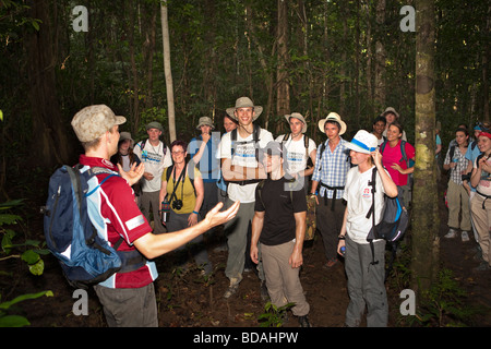 Indonesia Sulawesi Operation Wallacea guide talking to sixth form students walking through forest - Stock Photo
