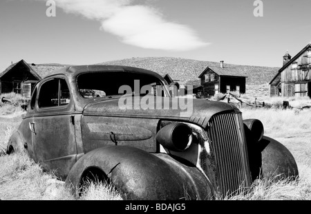 Abandoned, rusted out coupe in ghost town of Bodie, California - Black and White - Stock Photo