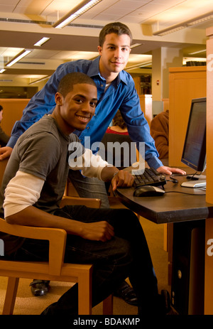 Ethnically diverse pair of men smiling  in the library - Stock Photo