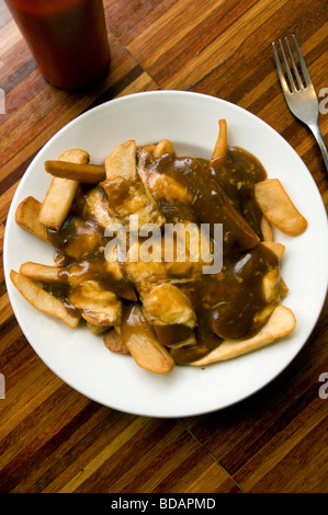 A plate of freshly served poutine - a Canadian delicacy consisting of french fries, gravy and cheese - at a restaurant - Stock Photo