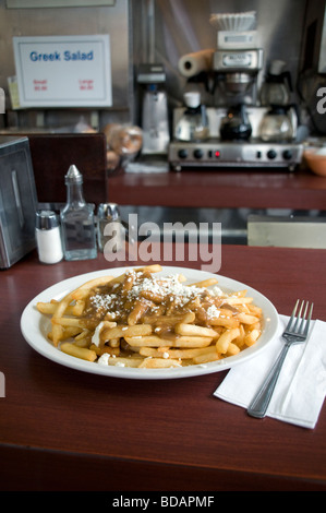 A plate of poutine, an iconic Canadian food, served at a traditional diner in Toronto, Canada. - Stock Photo