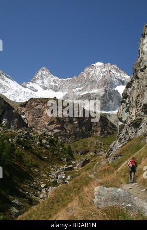Female Hiker walking in direktion Wellenkuppe Zermatt Valis Switzerland - Stock Photo