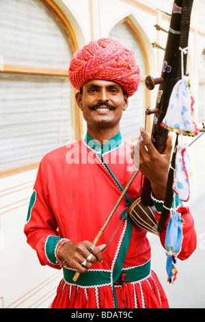 Mid adult man playing sarangi in a palace, City Palace, Jaipur, Rajasthan, India - Stock Photo