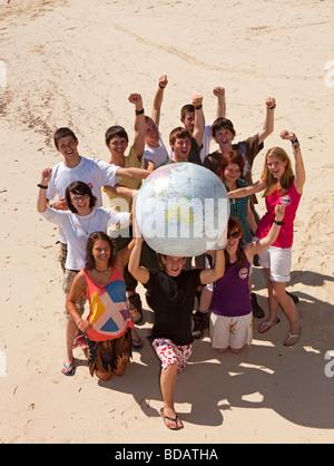 Indonesia Sulawesi Wakatobi National Park Hoga island Operation Wallacea volunteers with inflatable globe - Stock Photo