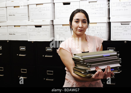 Portrait of a file clerk holding a stack of files in front of a filing cabinet - Stock Photo