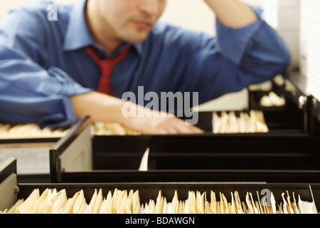Businessman searching files in a filling cabinet - Stock Photo