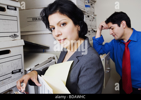 Side profile of a businesswoman searching for files with a businessman standing near her - Stock Photo